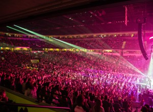 Arena full of people with pink lights shining on stage